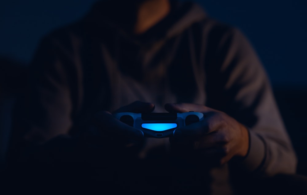 person wearing brown pullover using teal and black Sony PS4 Dualshock