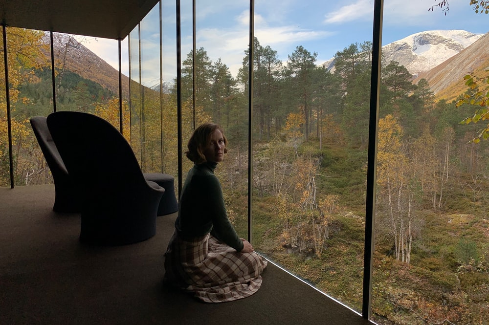 woman wearing black long-sleeved shirt sitting beside glass wall