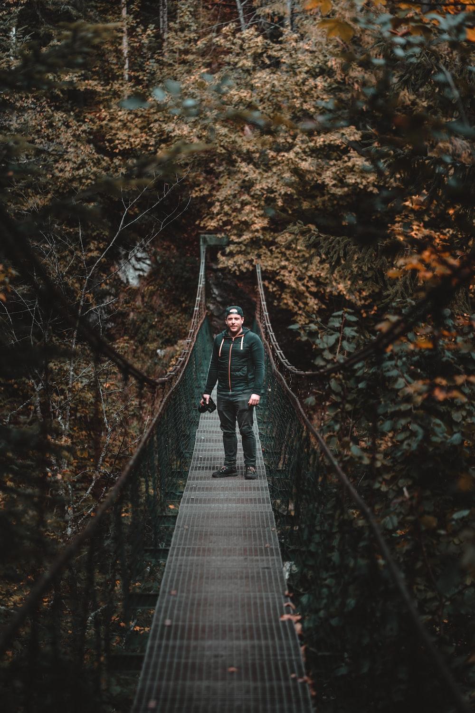 man wearing jacket and pants standing on bridge near trees