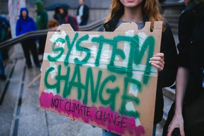 woman holding system change not climate change sign