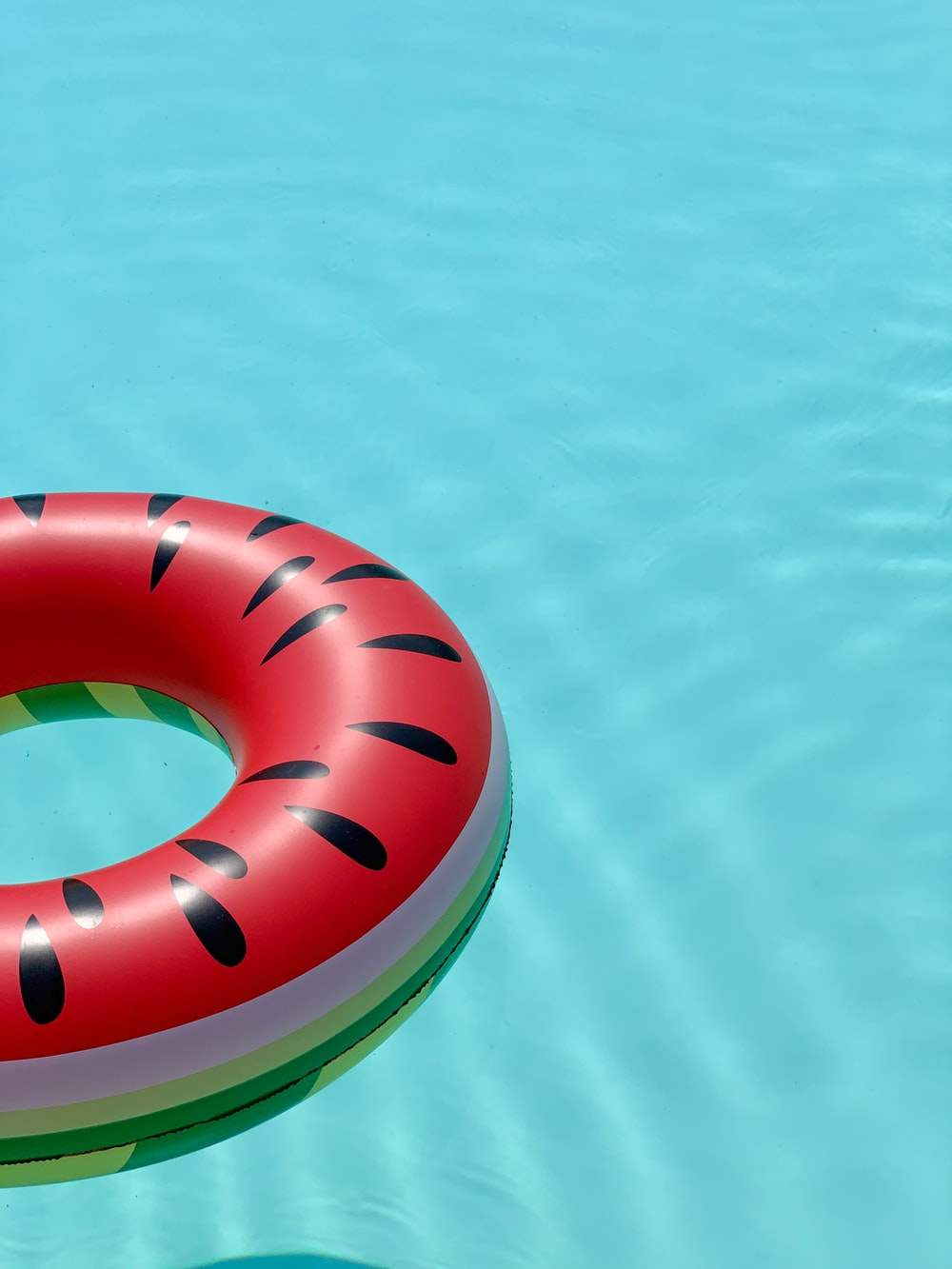 red and green lifebuoy on swimming pool