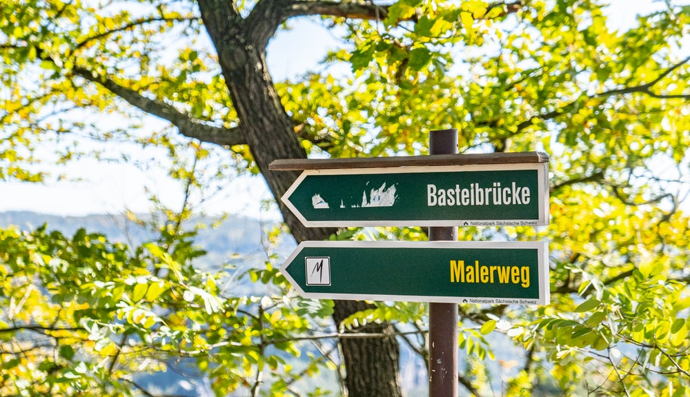 Bastelbrucke and Malerweg signboards on post near tree during day