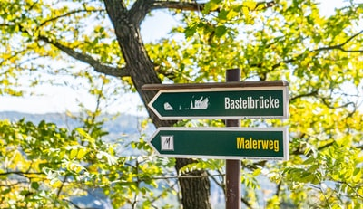 Bastelbrucke and Malerweg signboards on post near tree during day