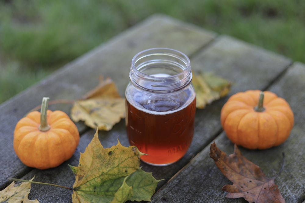 jar of honey beside two pumpkins