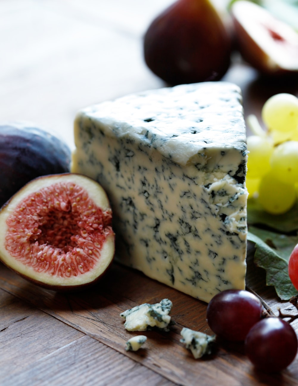 fruits and cheese on wooden surface