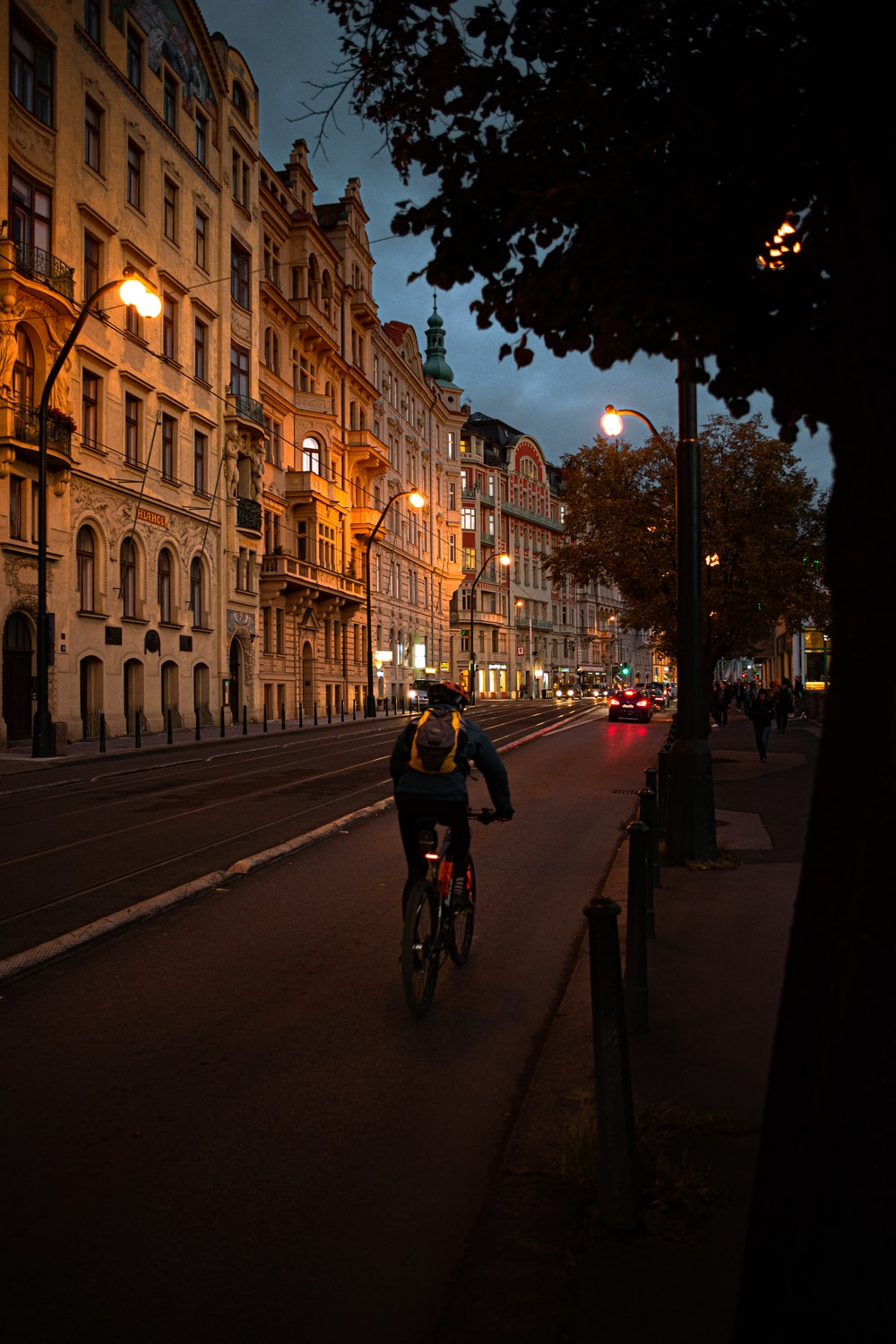 man riding bicycle beside buildings during nighttime