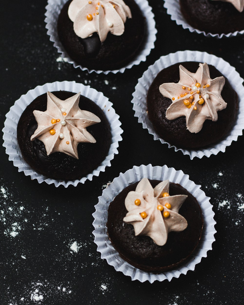 cupcakes with icings on black surface