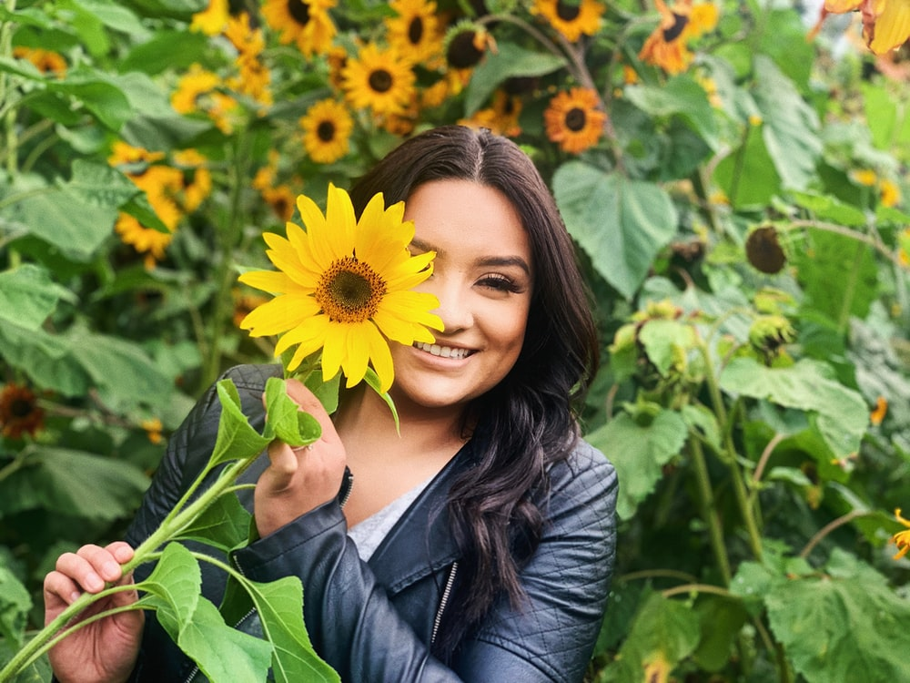 smiling woman holds sunflower
