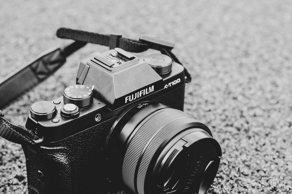 black and gray Fujifilm SLR camera on concrete surface
