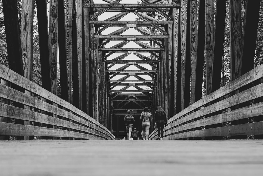 grayscale photography of people walking on bridge