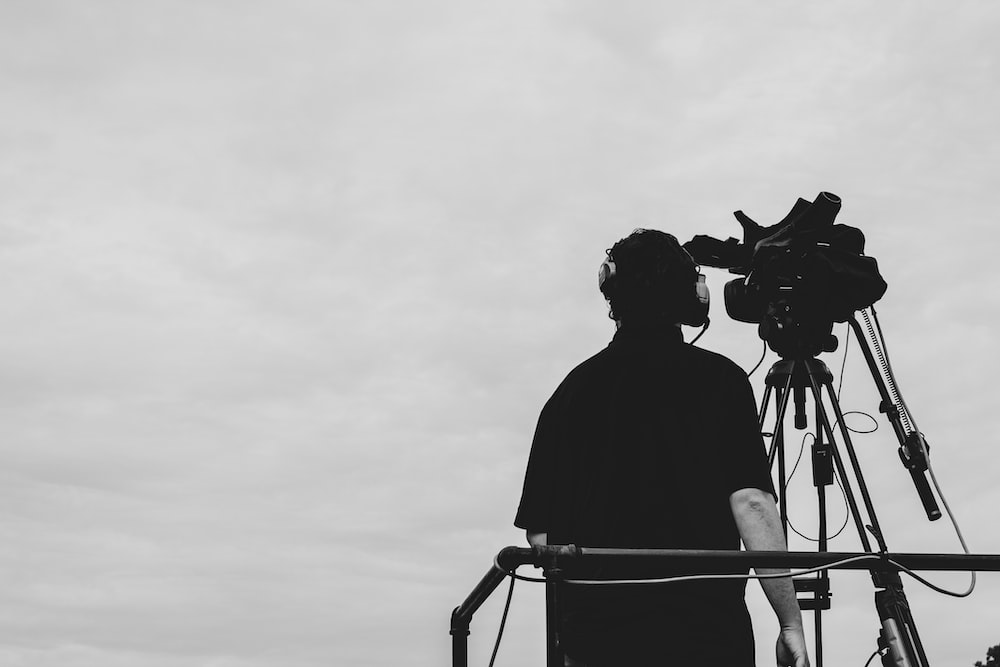 greyscale photography of man standing beside video camera