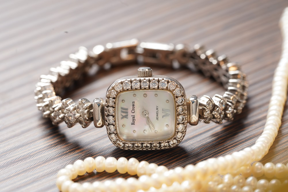 square gold-colored analog watch with bezel
