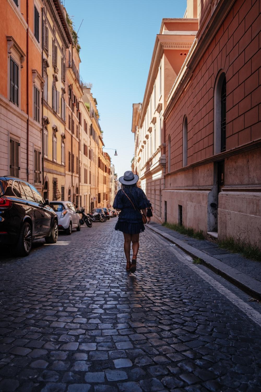 woman waling near concrete buildings