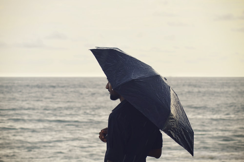Person Holding Umbrella Near Body Of Water Photo Free Canopy Image On Unsplash