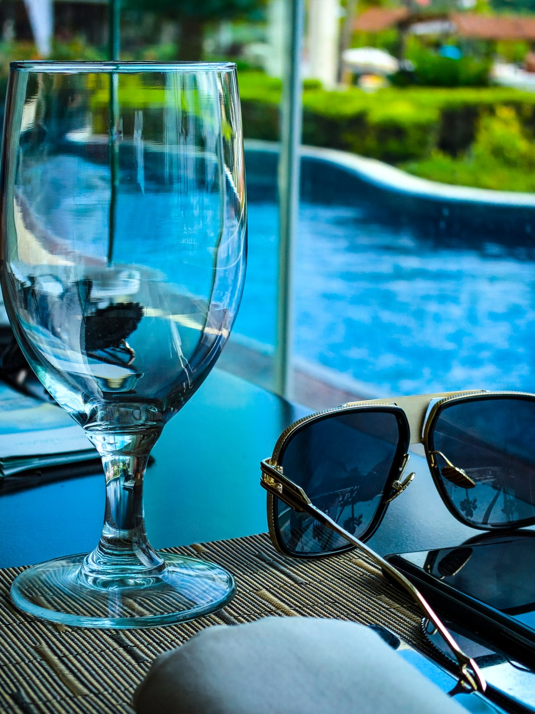High fashion sunglasses, goblet and phone resting on a restaurant table. In front of a pool, grass and Palm trees.