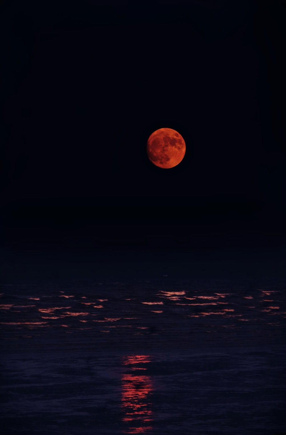 red moon and body of water