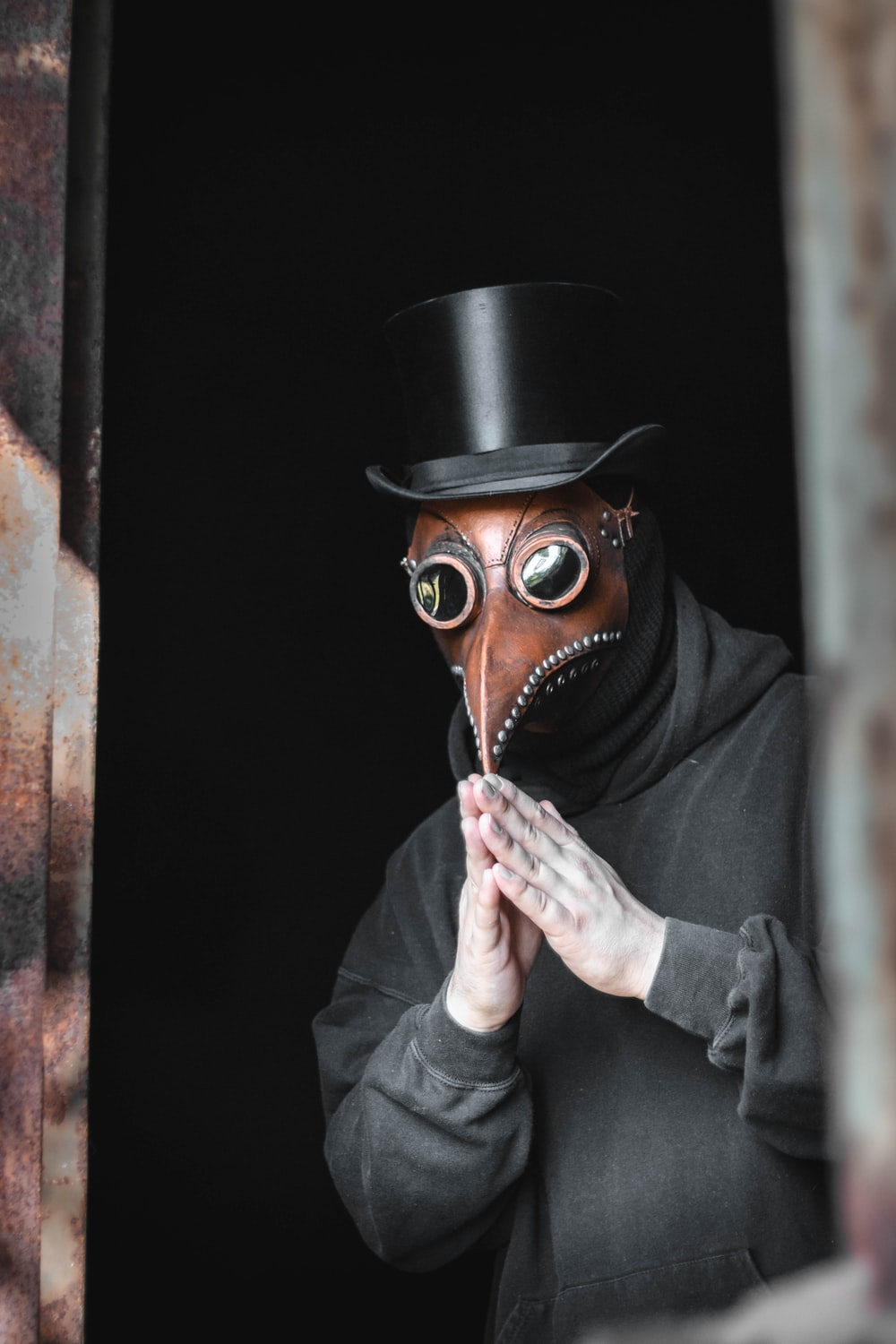 person wearing top hat and animal mask touching their own fingertips