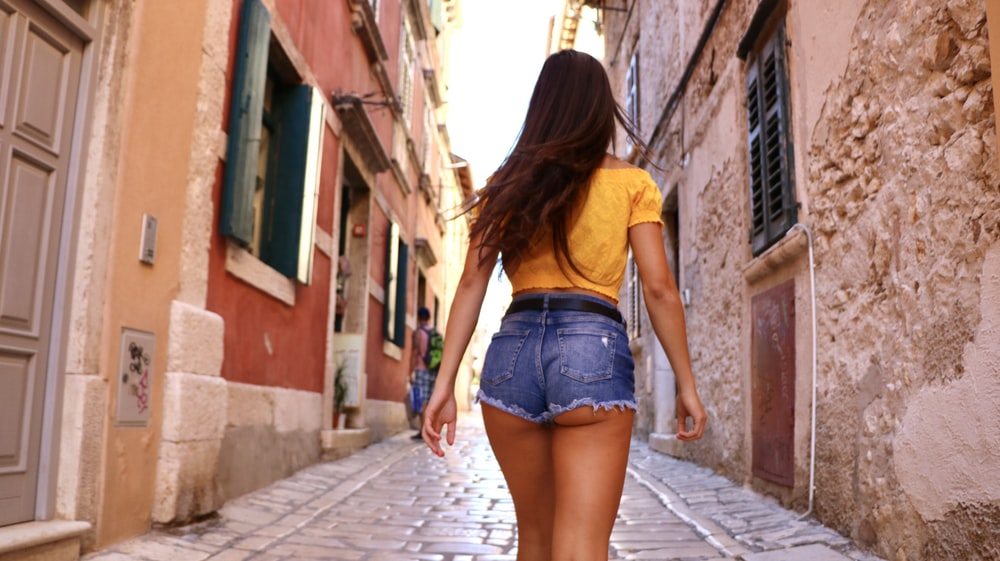 woman standing near brown concrete buildings
