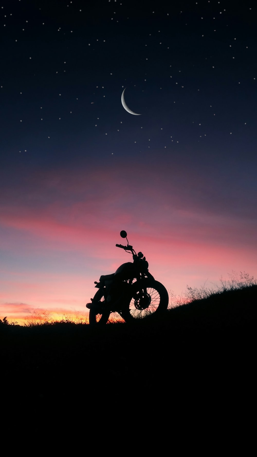 silhouette of motorcycle on grass field at night
