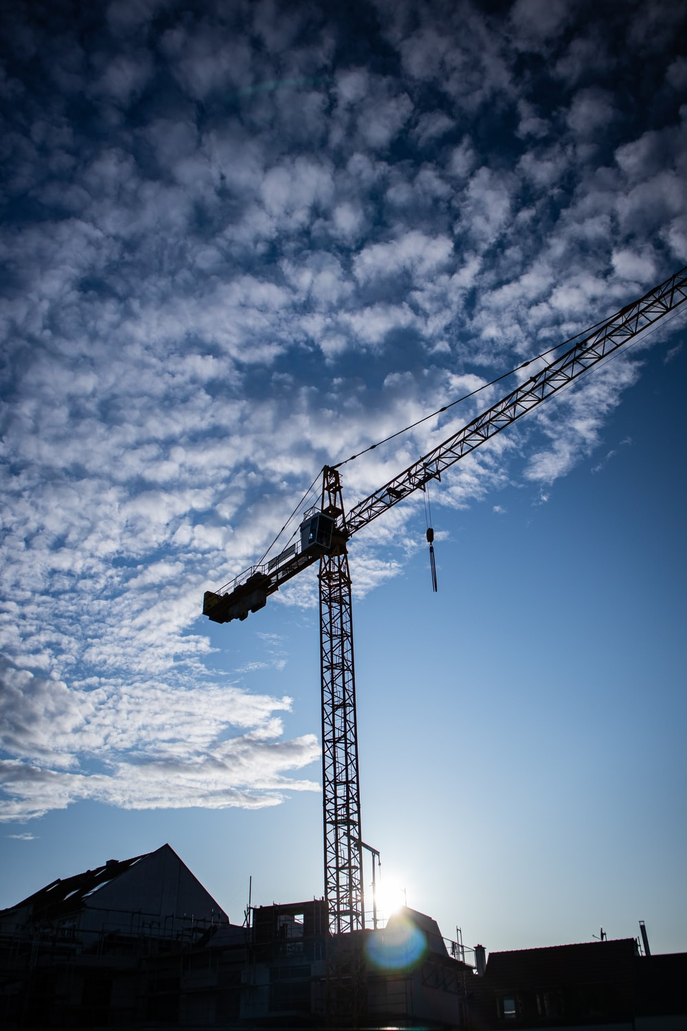 black industrial crane under white and blue sky during daytime