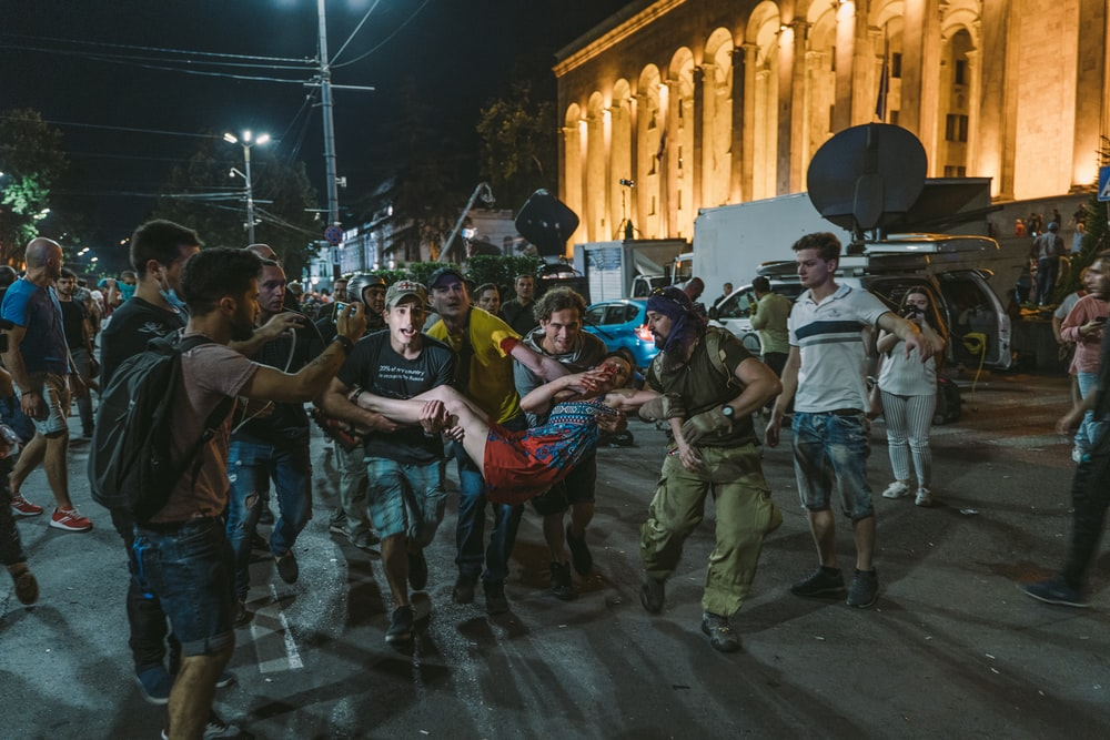 people carrying man near building