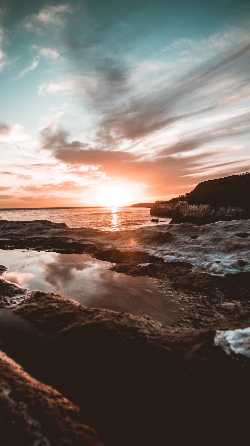 rocks in ocean during golden hour