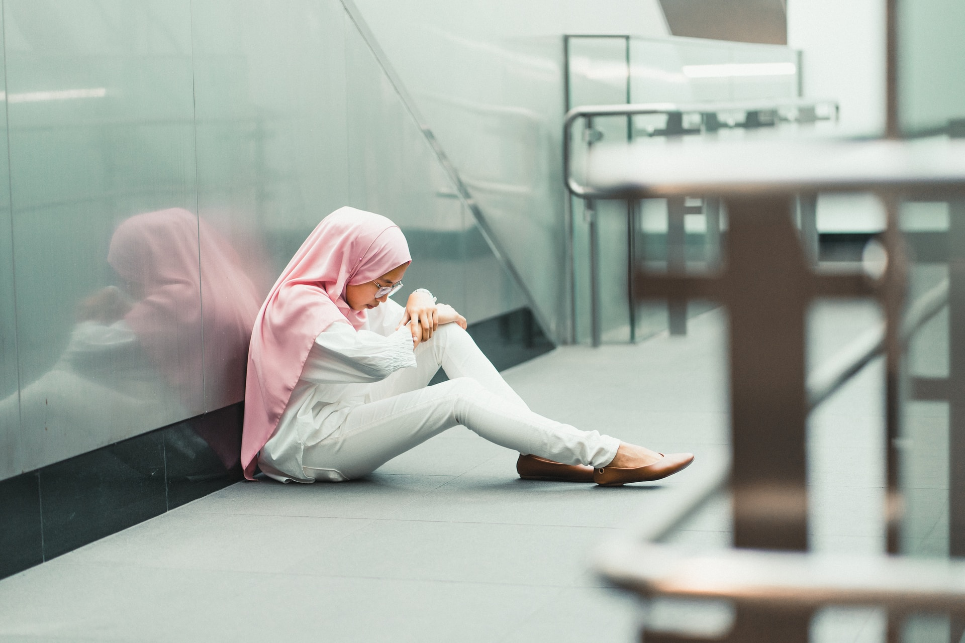woman sitting on floor while leaning on glass wall