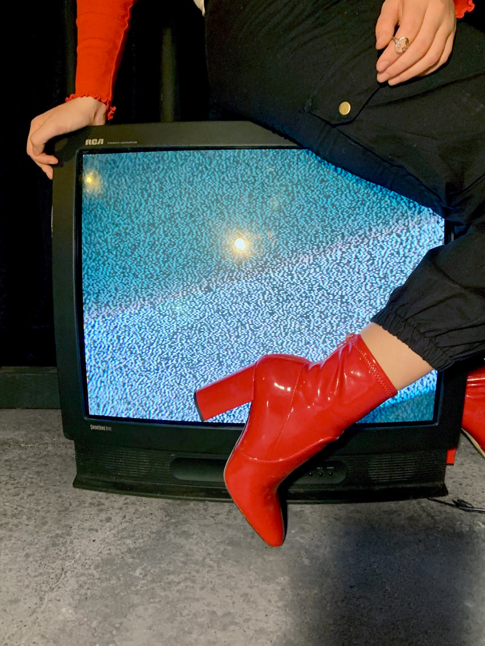 woman sitting on black CRT TV