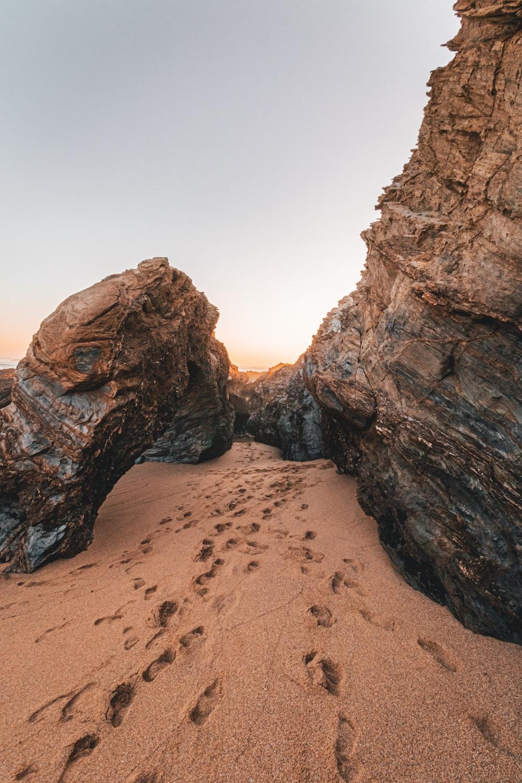footprints in sand near rocks