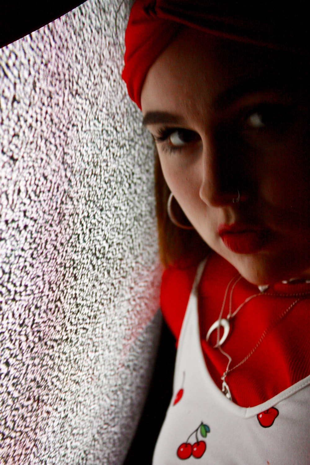 woman in red and white top facing by a CRT TV