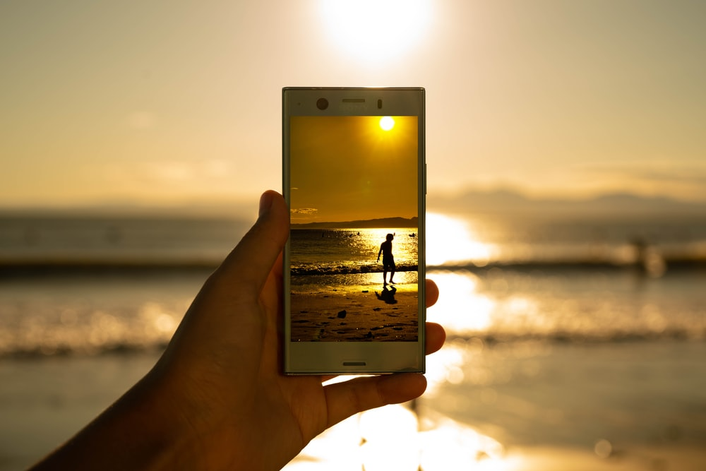 person holding phone showing person on seashore