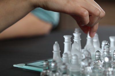 person touching chess piece