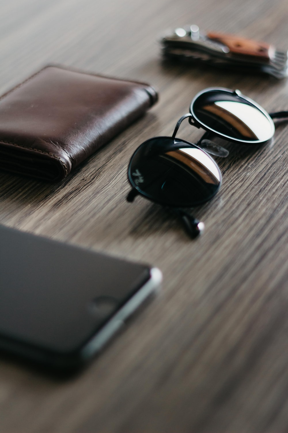 black Ray-Ban sunglasses beside brown leather wallet