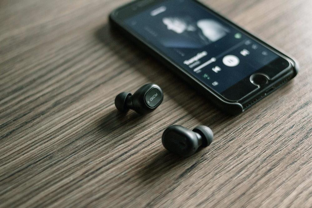 pair of Bluetooth earphones beside phone