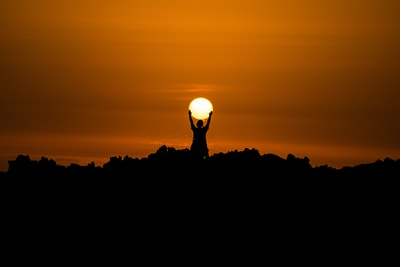silhouette of person holding dun sun teams background