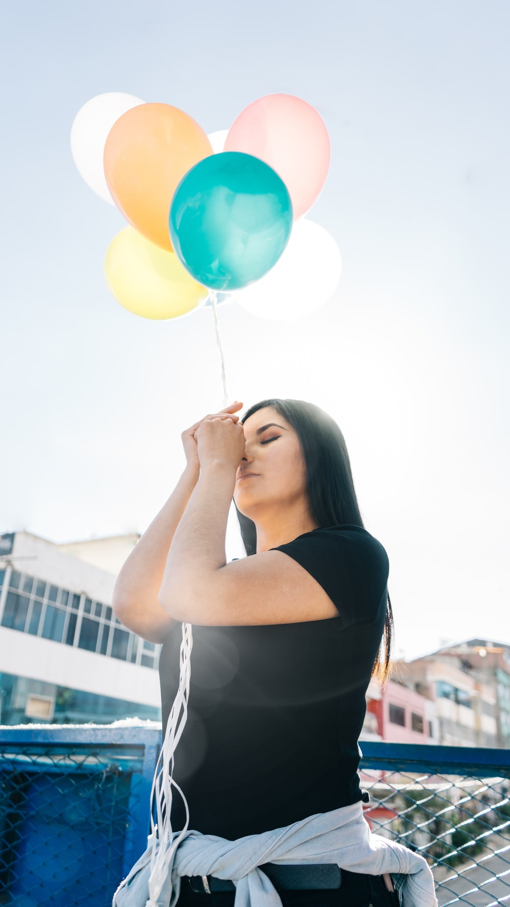 woman in black top holding balloons