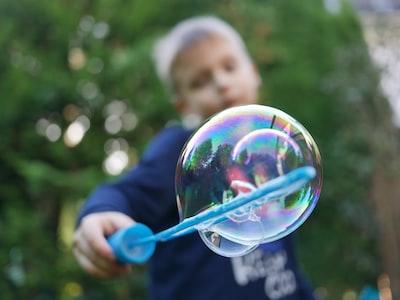 boy playing bubbles near tree