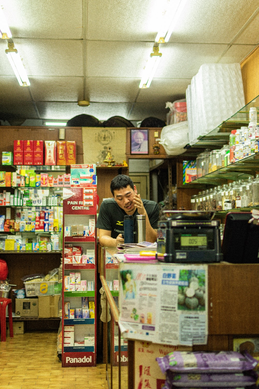 man wearing black shirt leaning on display counter