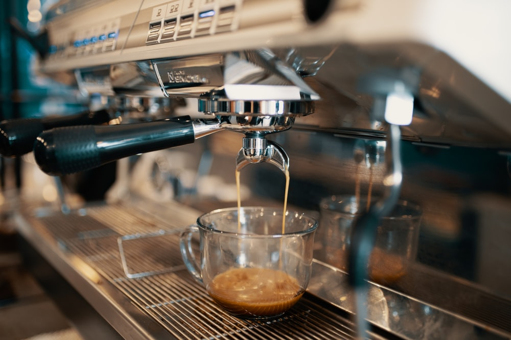 clear glass cup pouring coffee from expresso maker