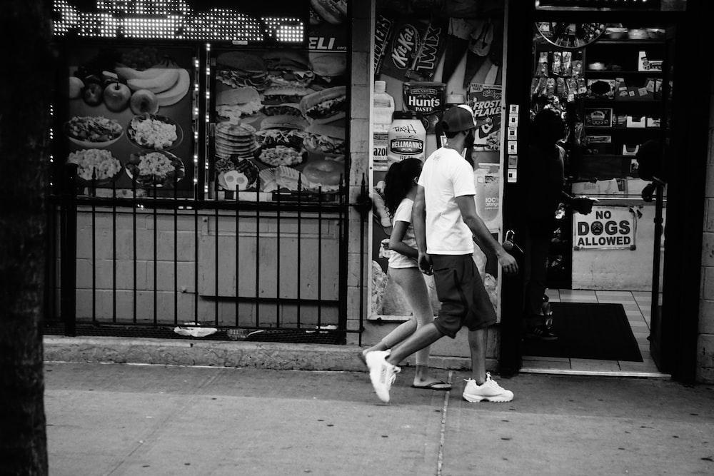 man and child walking on street