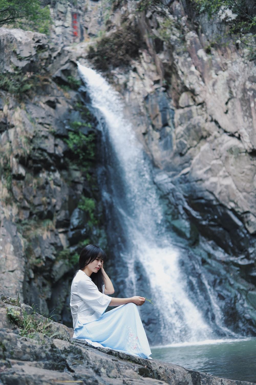 woman wearing white dress across waterfalls