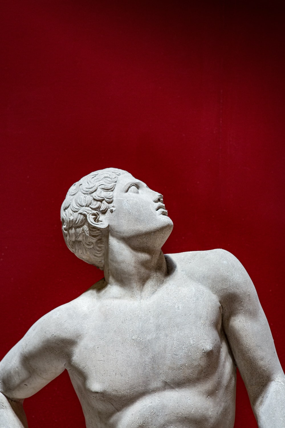 Grecian male statue looks up on red background