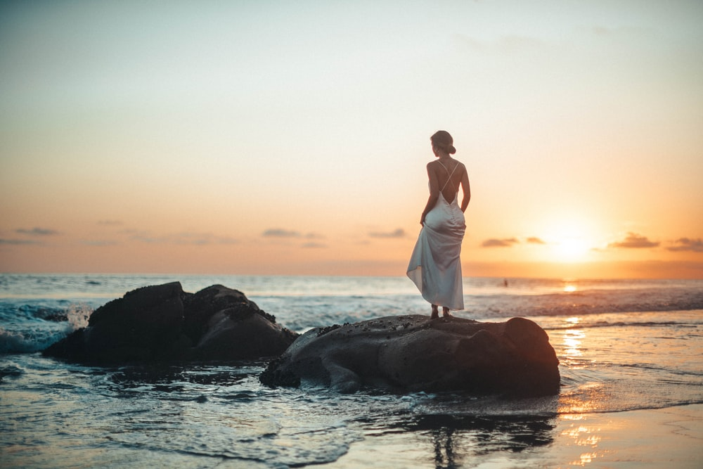 woman standing on rock during golden hour