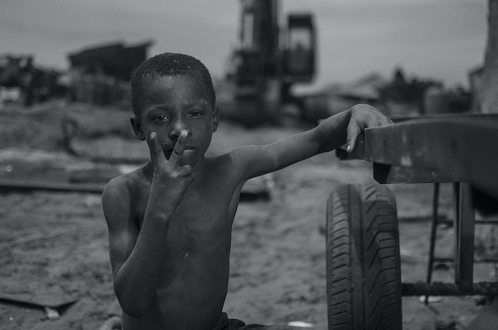 boy sits near the vehicle