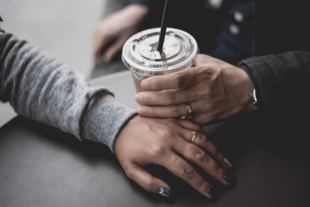 person holding drink with straw beside person's hand