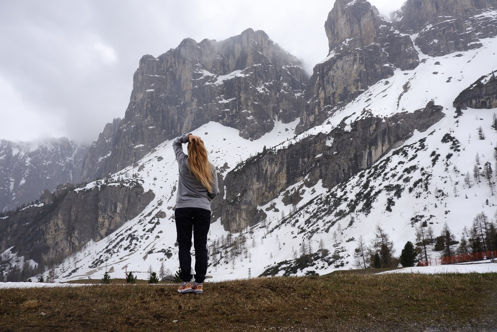 standing woman facing mountains during daytime