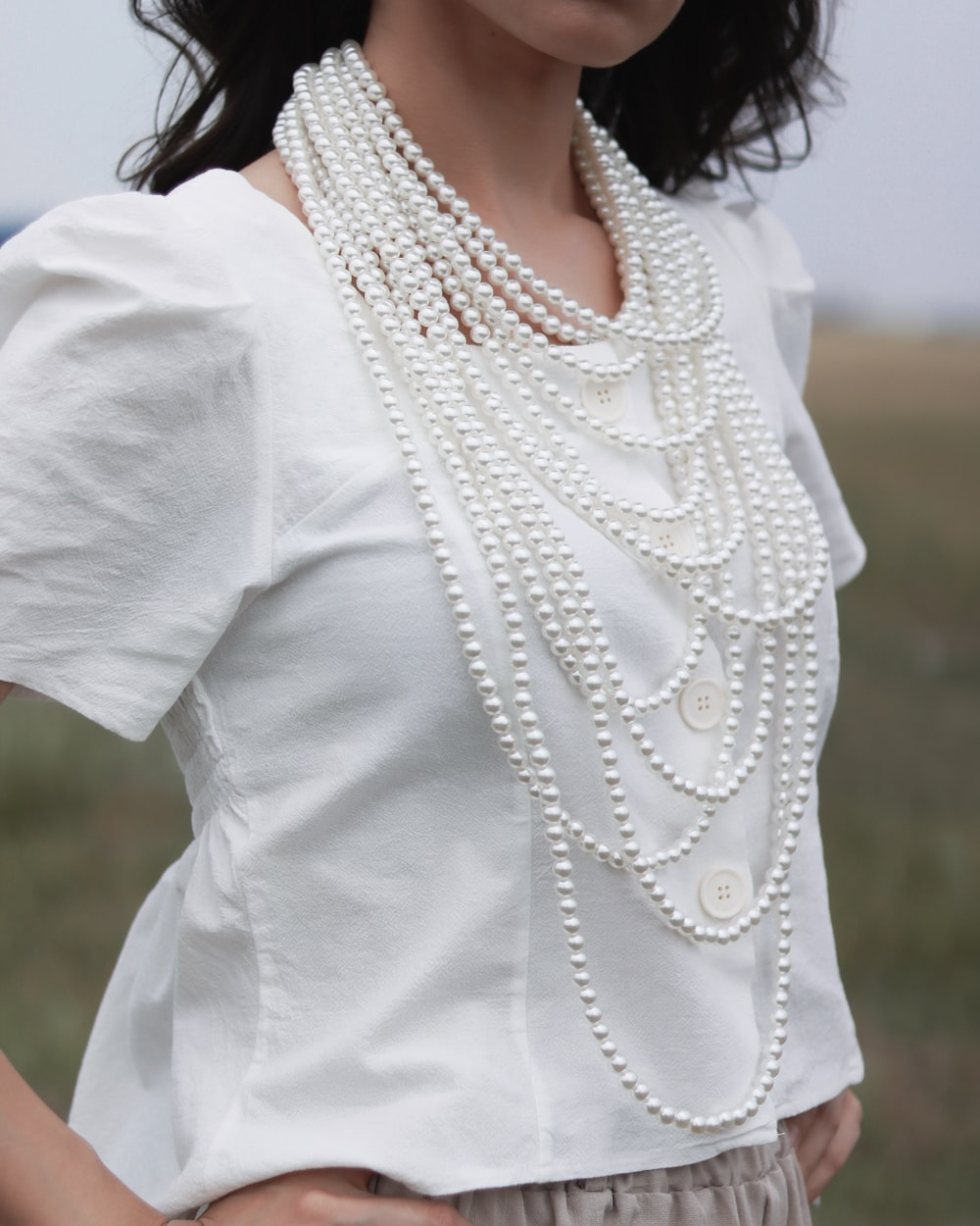 woman wearing white blouse and white pearl necklace