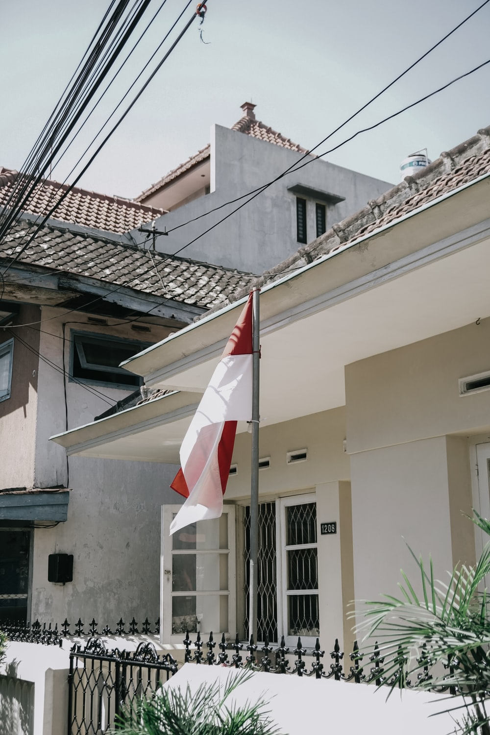 white and red flag beside house