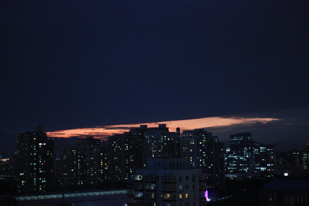 silhouette of city buildings during nighttime