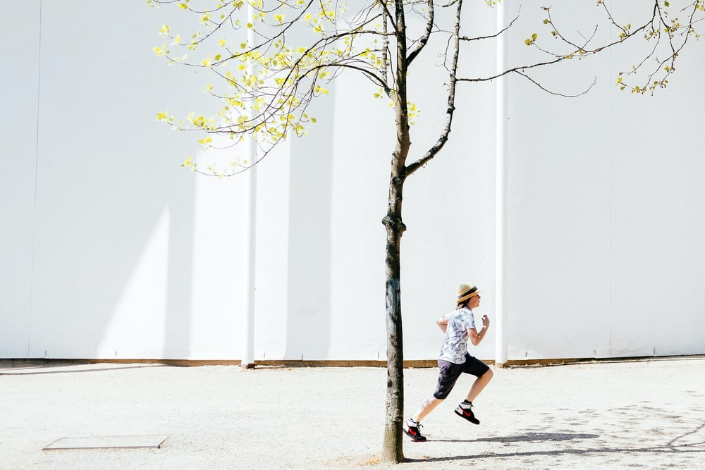 person in white T-shirt running